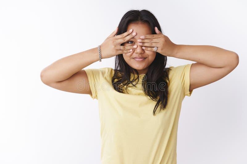 年轻玻利尼西亚女孩盖子眼睛和偷看通过微笑的手指广泛地anticiapting的惊人的惊奇身分 免版税库存照片