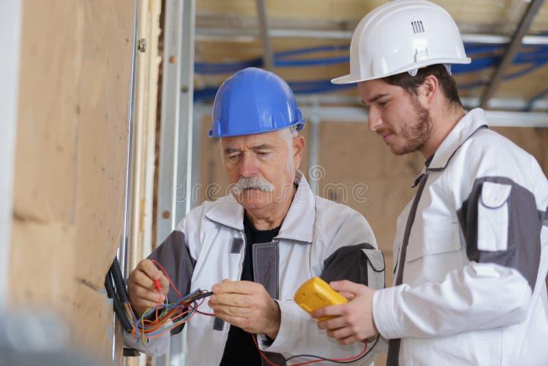 年轻电工和资深监督员在工作 免版税图库摄影