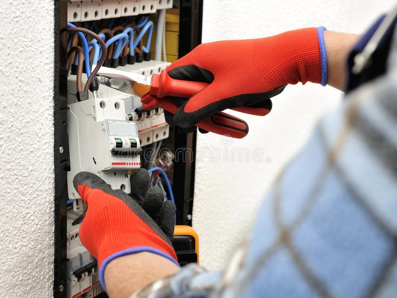 年轻电工技术员在一个电子盘区的工作与 免版税库存照片