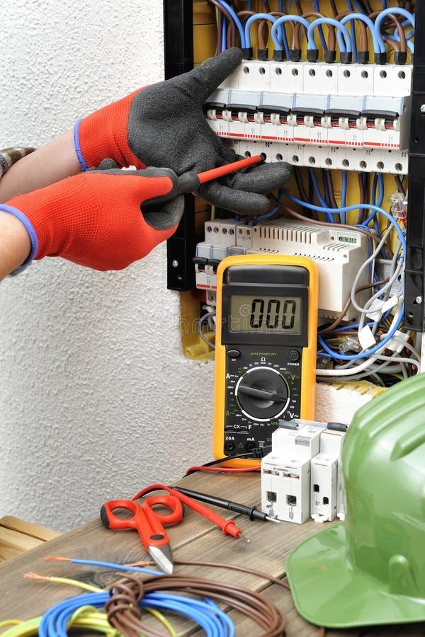 年轻电工技术员在一个电子盘区的工作与 免版税库存图片