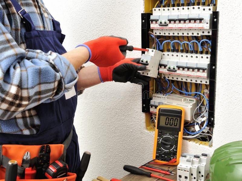 年轻电工技术员在一个电子盘区的工作与 库存图片
