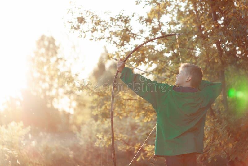年轻男孩、射击与手工制造弓箭在目标在日落,夏令时户外 库存照片