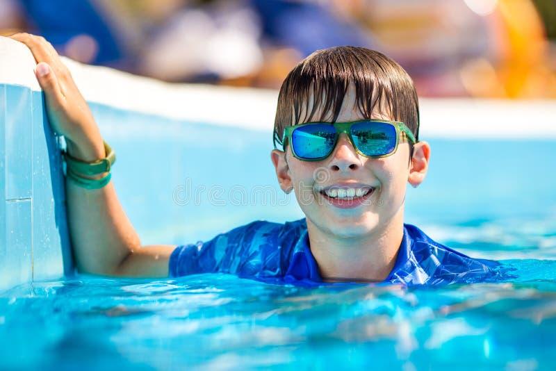 年轻男孩使用Google拿着游泳场边缘  在刷新的水中享受时间 免版税库存图片