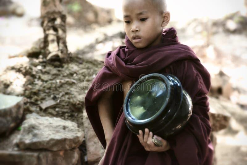 年轻男孩修士向午餐求助在Kalaywa Tawya修道院在仰光 免版税库存照片