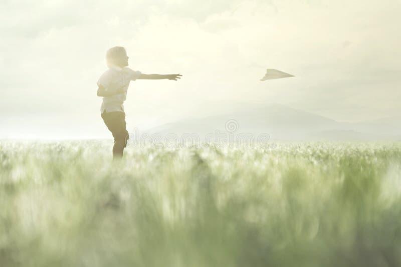年轻男孩做他的纸飞机在草甸飞行 免版税图库摄影