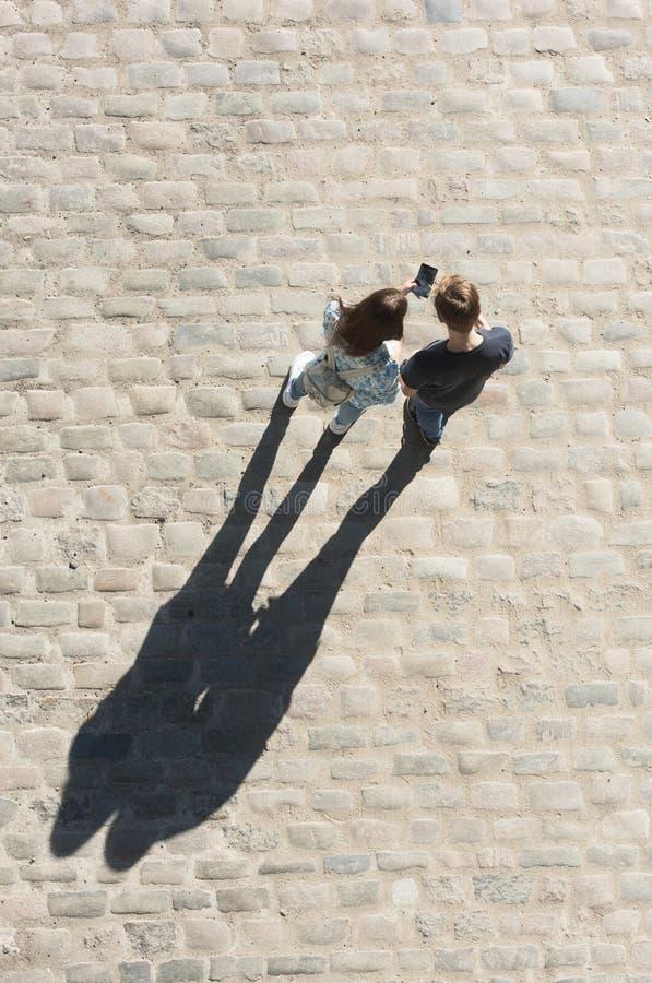 年轻男孩和女孩看手机n街道 免版税图库摄影