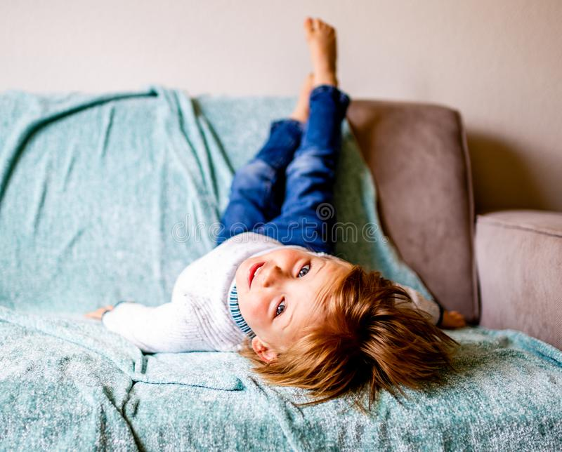年轻男孩在长沙发放置 免版税库存照片