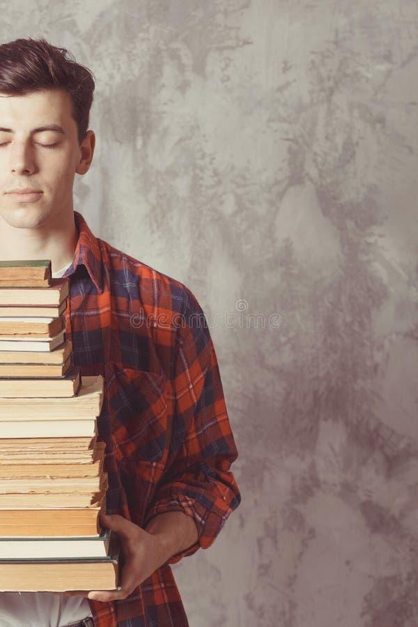 年轻男孩学生举行许多书 人想要学会,有教育 r 研究在学校 男性为教训做准备 免版税库存照片