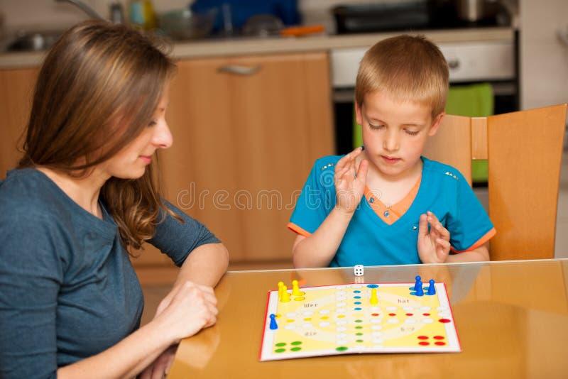 年轻男孩打与他的母亲的卢多比赛在livingro的一张桌上 免版税库存照片