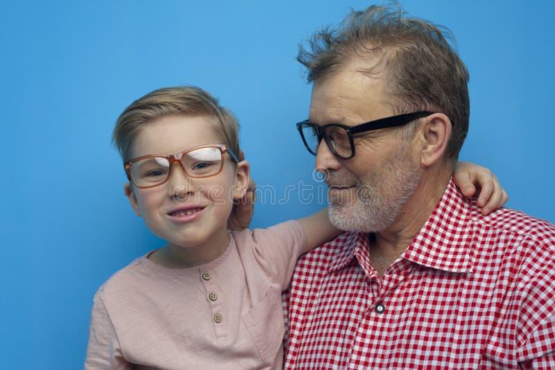 年轻男孩拥抱微笑对照相机的祖父 免版税图库摄影