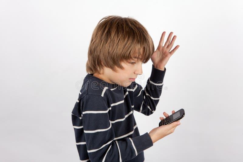 年轻男孩拿着一个基本的手机的和不太满意对它 免版税库存照片