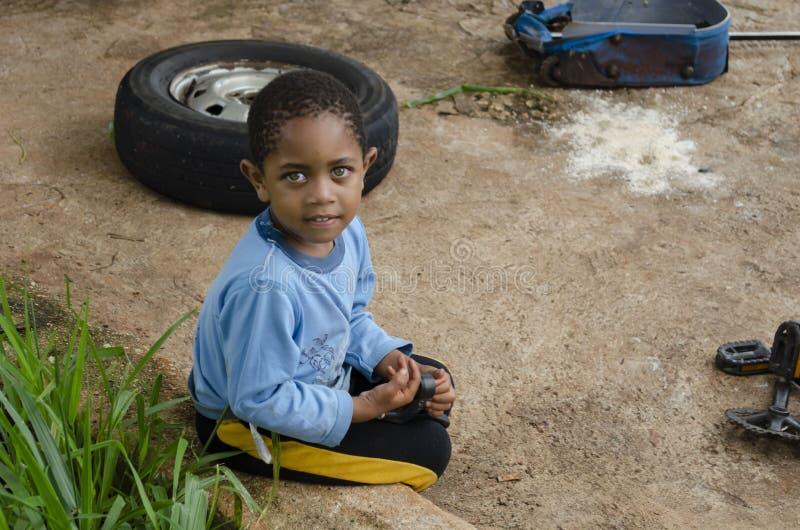 年轻男孩直立的东西坐墙壁外部 免版税图库摄影