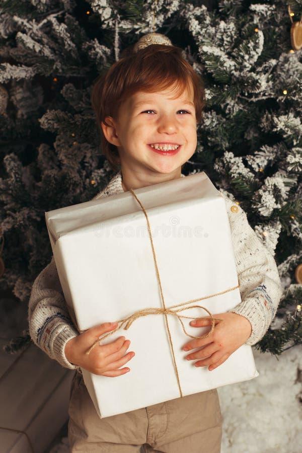 年轻男孩舒适大气的圣诞节画象在圣诞树附近的 拿着白色礼物盒的逗人喜爱的小孩 库存图片