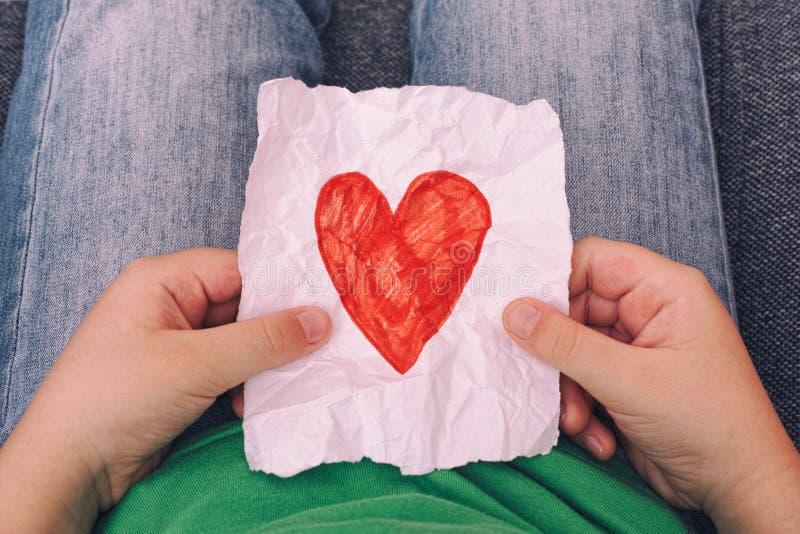 年轻男孩藏品弄皱了纸与红色心脏形状的 免版税库存图片