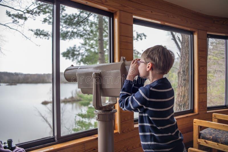 年轻男孩观鸟通过范围 库存图片