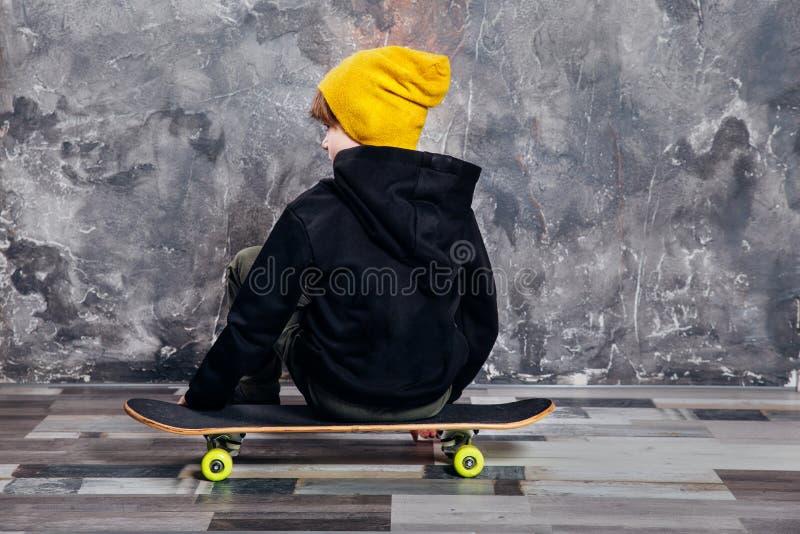 年轻男孩青少年的青年时期趋向与滑板的演播室画象 库存照片