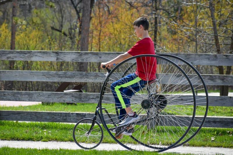 年轻男孩,古板的自行车骑马 库存图片
