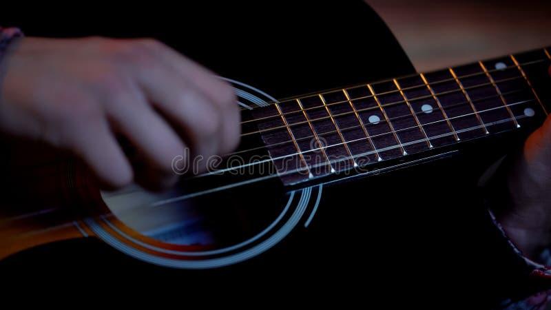 年轻男性使用的声学吉他,关于音乐家事业,特写镜头的梦想 免版税库存图片