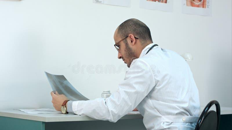 年轻男性医生审查的胸部X光图象 库存图片