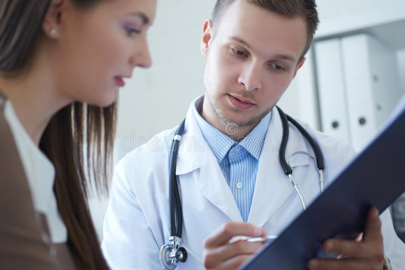 年轻男性医生拿着一张剪贴板并且与一名女性患者谈话,坐在诊所的候诊室 免版税库存图片