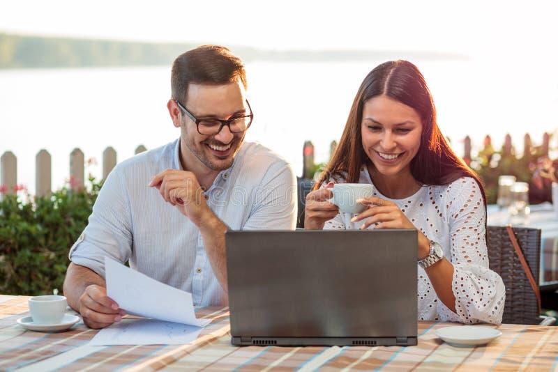 年轻男性和女性商人开一次偶然工作会议在河沿咖啡馆 免版税图库摄影