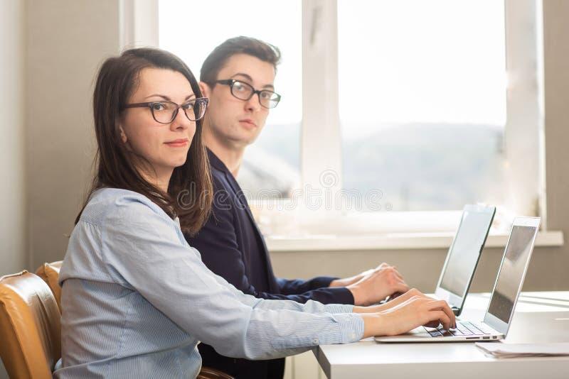 年轻男性和女性坐在计算机显示器后的商务伙伴 免版税库存图片