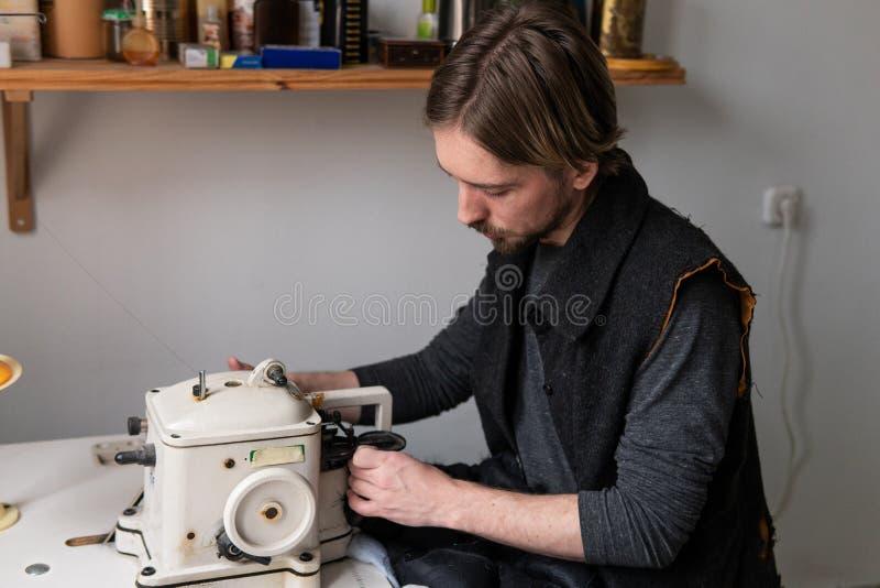年轻男性在更加毛茸的机器的裁缝缝合的毛皮 库存图片