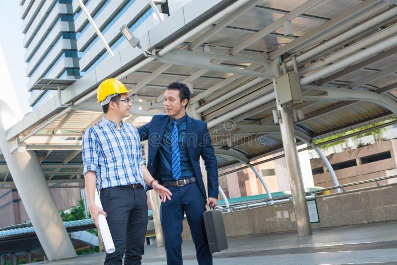 年轻男性建筑师谈论与商人在Constructio 免版税库存照片