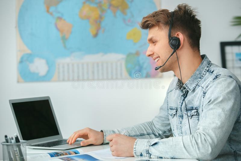 年轻男性旅行代理人顾问在使用耳机的游览机构中 免版税库存照片