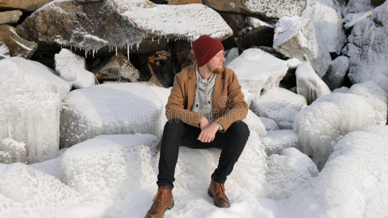 年轻男性渔夫坐冰 免版税库存图片