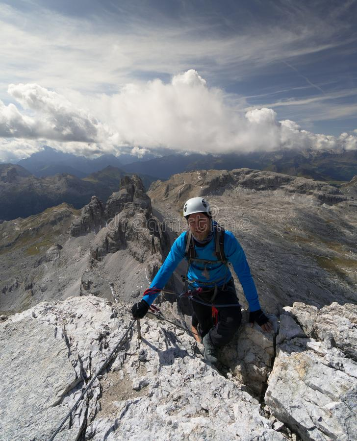 年轻男性登山人在做a以后到达山顶通过在意大利白云岩的Ferrata 库存图片