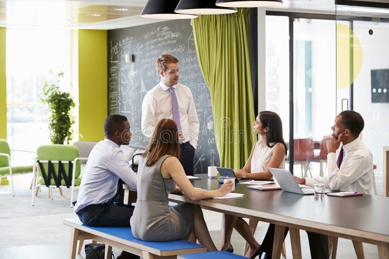 年轻男性经理对同事演讲在非正式会议上 图库摄影