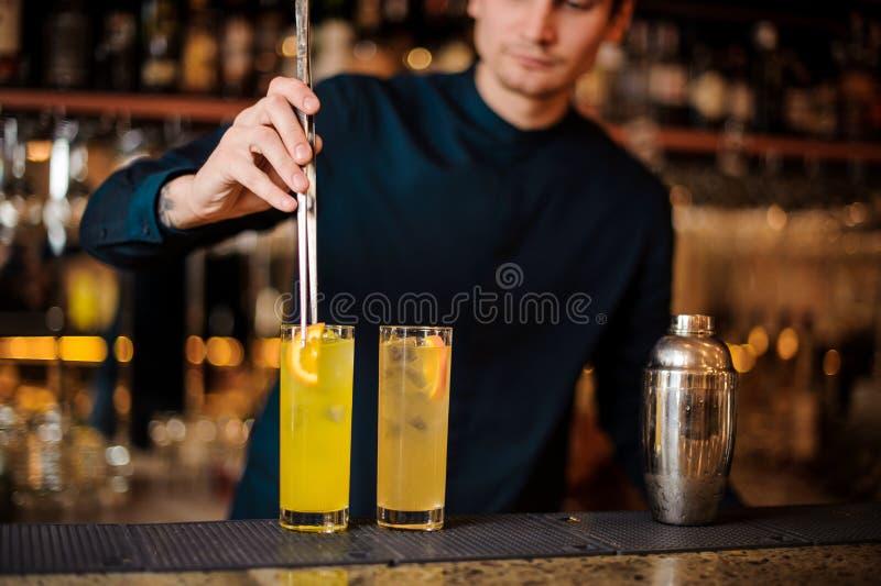 年轻男服务员准备两个酒精鸡尾酒,增加桔子片断  免版税库存图片
