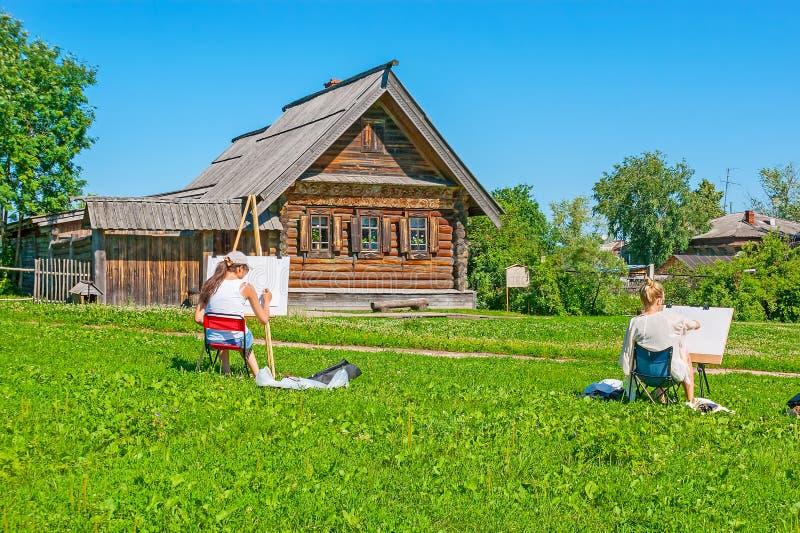年轻画家在木建筑学苏兹达尔博物馆  库存照片