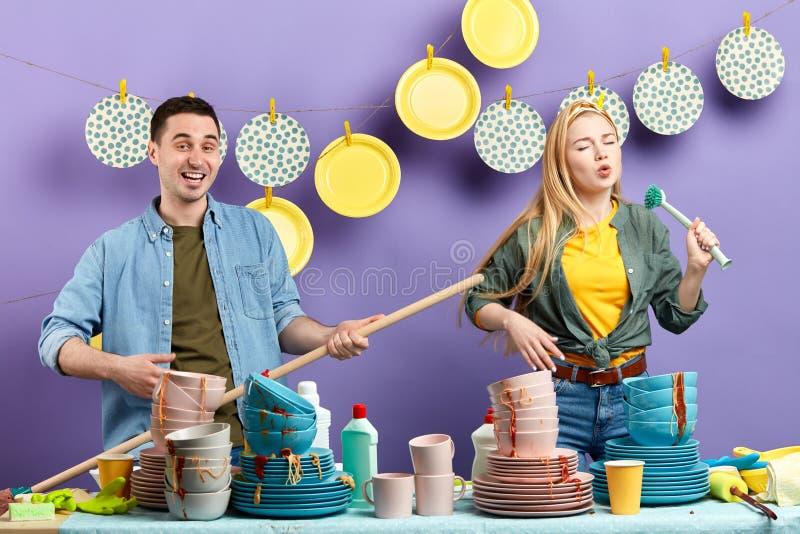 年轻疯狂的夫妇获得乐趣在有现代内部的厨房 E 免版税库存图片