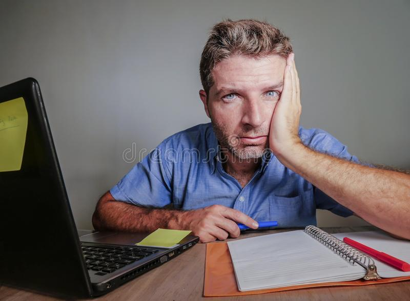 年轻疯狂被注重的和被淹没的人工作杂乱在办公桌绝望与便携式计算机遭受的消沉frustrat 免版税库存图片
