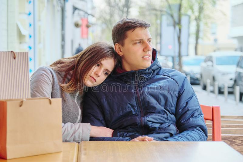 年轻疲乏的加上在街道咖啡馆、等待的咖啡和茶的购物带来 库存照片