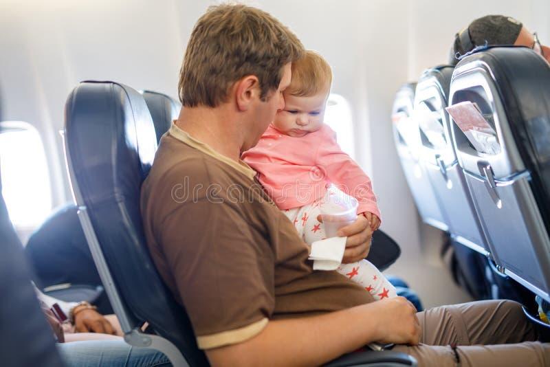 年轻疲乏的父亲和他哭泣的小女儿在飞行期间在继续假期的飞机 使用的爸爸举行和 免版税库存照片