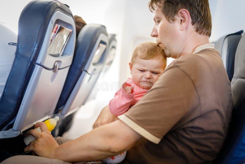 年轻疲乏的父亲和他哭泣的小女儿在飞行期间在继续假期的飞机 免版税库存照片
