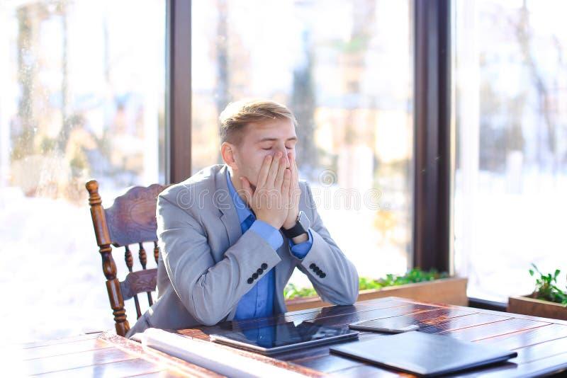 年轻疲乏的经理有断裂在与卷轴式记录纸,片剂的咖啡馆 库存照片