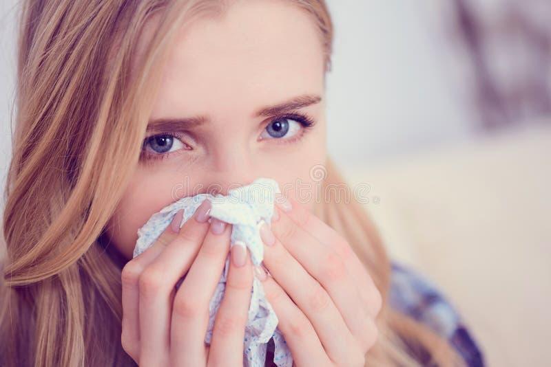 年轻病态的白种人妇女喷嚏在家在有寒冷的沙发 女孩吹她的鼻子的使用的薄纸 医疗和 图库摄影