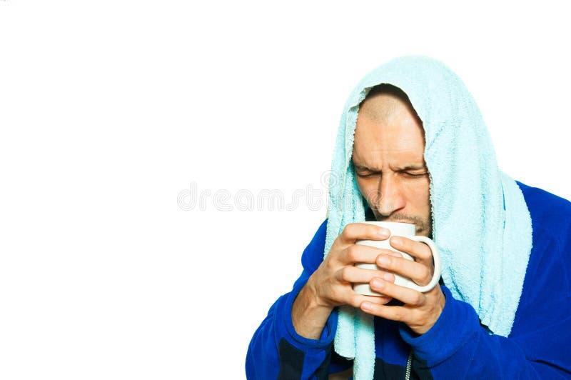 年轻病的人有感冒流感,并且他喝着一个杯子热的茶,当他佩带在头和重冬天克洛时的毛巾 免版税库存照片