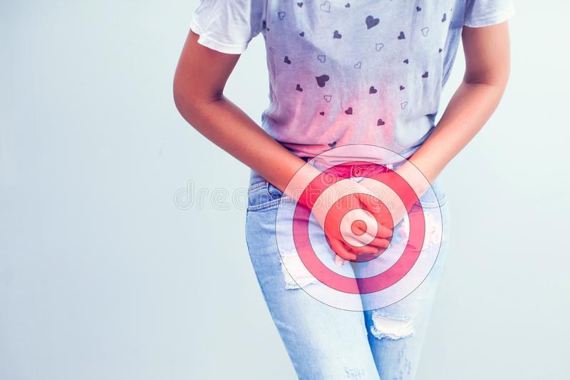 年轻病的妇女用举行按的手她的裤裆低ab 免版税库存图片