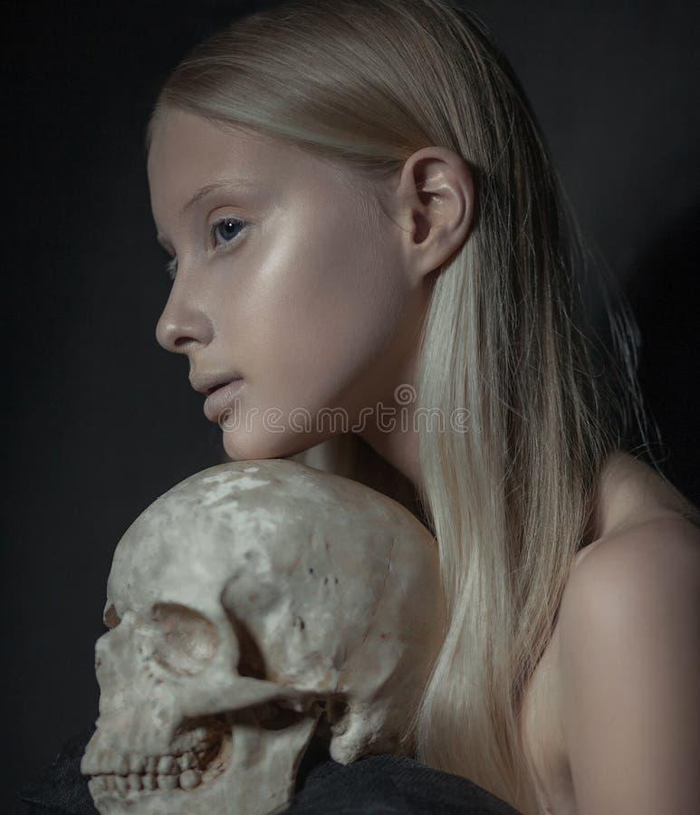 年轻白变种妇女画象外形的与人的头骨在她的手上 免版税库存图片