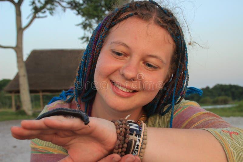 年轻白女孩有头发的旅客在蓝色猪尾在手边拿着一只蠕虫Julida 免版税库存照片