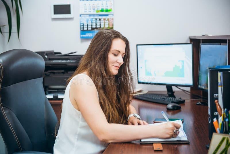 年轻白种人企业夫人坐她的工作场所在办公室 女性企业精神 满意的熟练的经理画象 库存图片