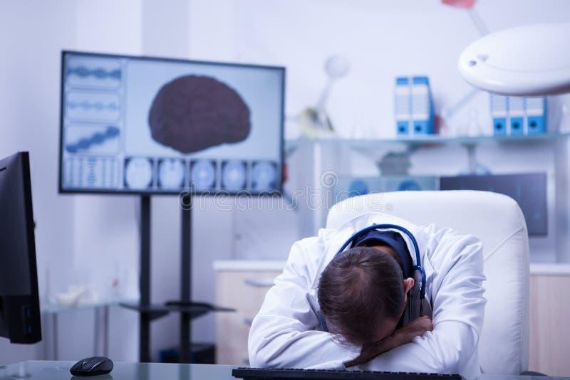 年轻白种人医生在这张书桌在有他的heand的医院坐书桌睡觉 免版税库存图片