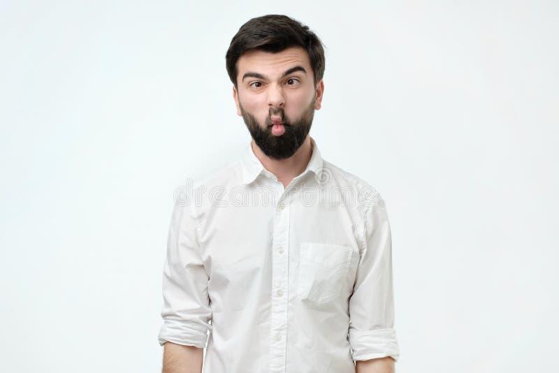 年轻白种人在做鱼的被隔绝的背景的行家人佩带的白色衬衫面对与嘴唇 免版税库存图片