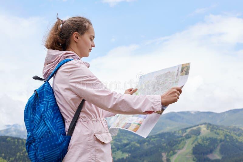 年轻白种人在小山的女性和地图室外射击有蓝色背包的在山和森林,看地图的徒步旅行者上和 免版税图库摄影