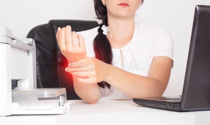 年轻白种人女孩办公室工作者在桡腕关节痛苦和炎症概念在手中举行,隧道综合症状 免版税库存照片